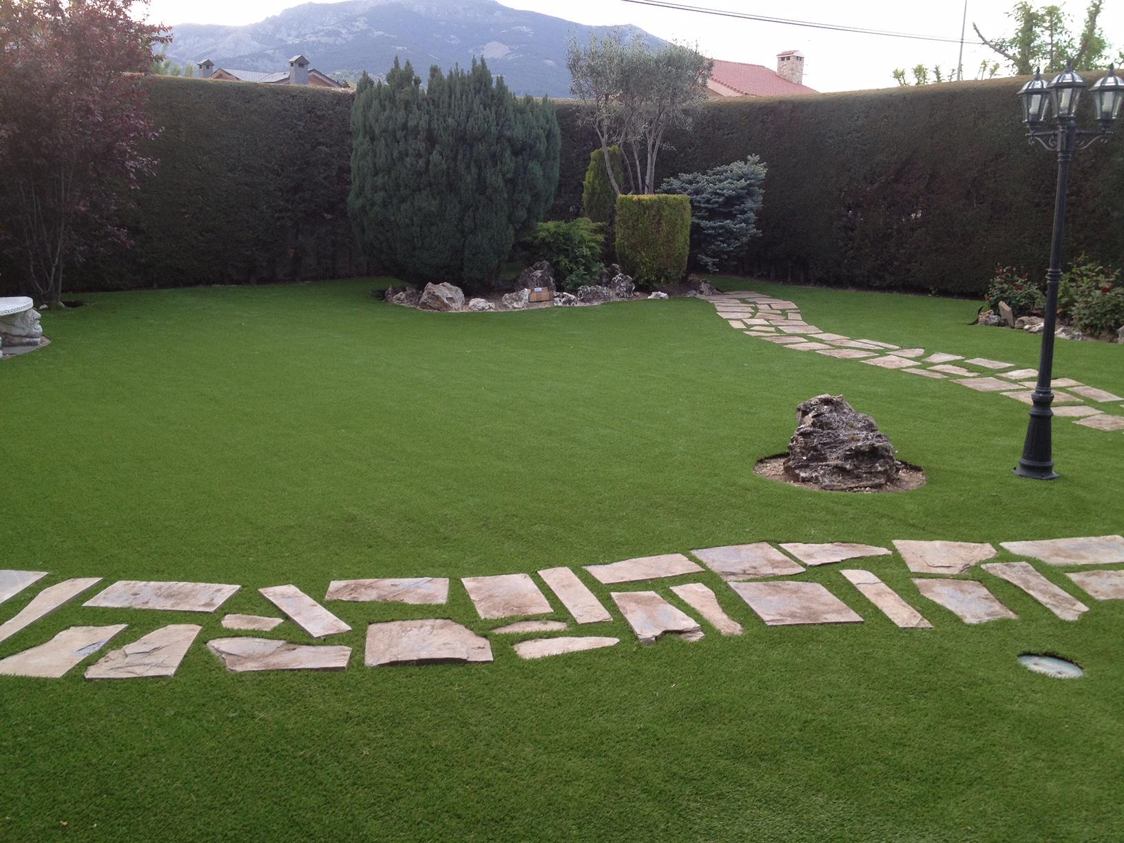 Instalaci n de c sped artificial en jard n con ariz nicas for Jardines cesped artificial piedras